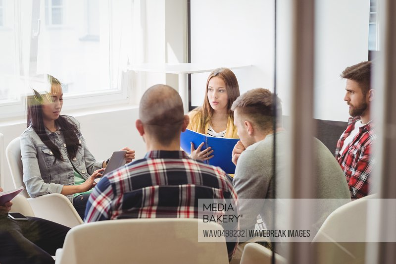 Creative business people in meeting room seen through glass