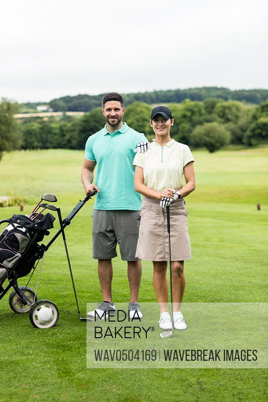 Portrait of smiling couple standing with golf club and bag in golf course
