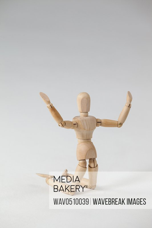 Wooden figurine kneeling with arms spread wide against white background