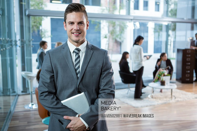 Portrait of handsome businessman holding digital table in office