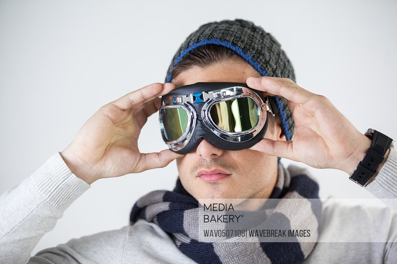 Man in winter clothing wearing aviator goggles against white background