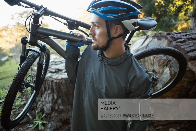 Male mountain biker carrying bicycle in the forest on a sunny day