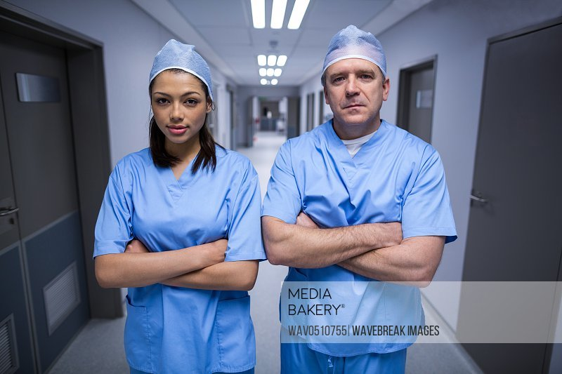 Portrait of surgeons standing with arms crossed in hospital corridor