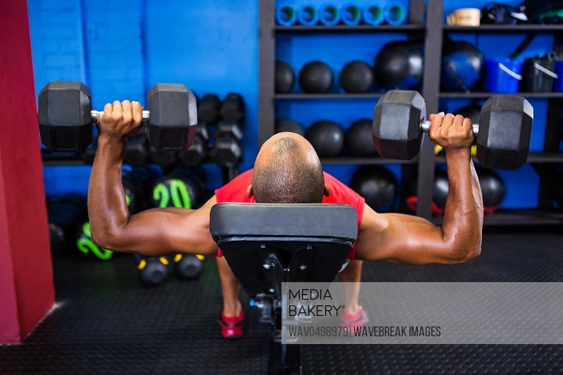 Man exercising with dumbbells on weight bench in gym