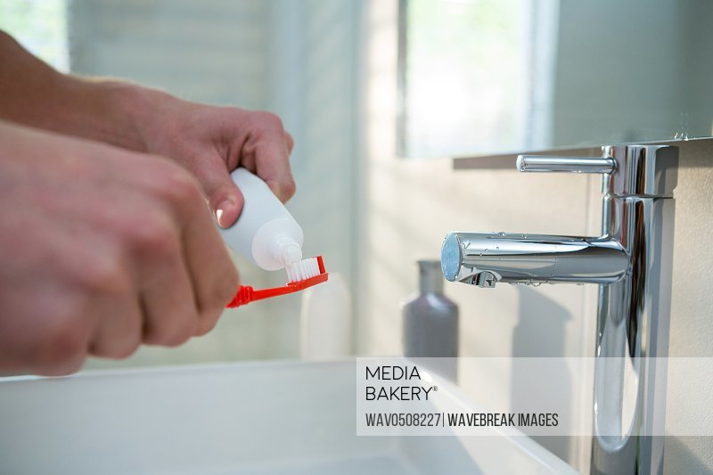 Man putting toothpaste on toothbrush in bathroom at home
