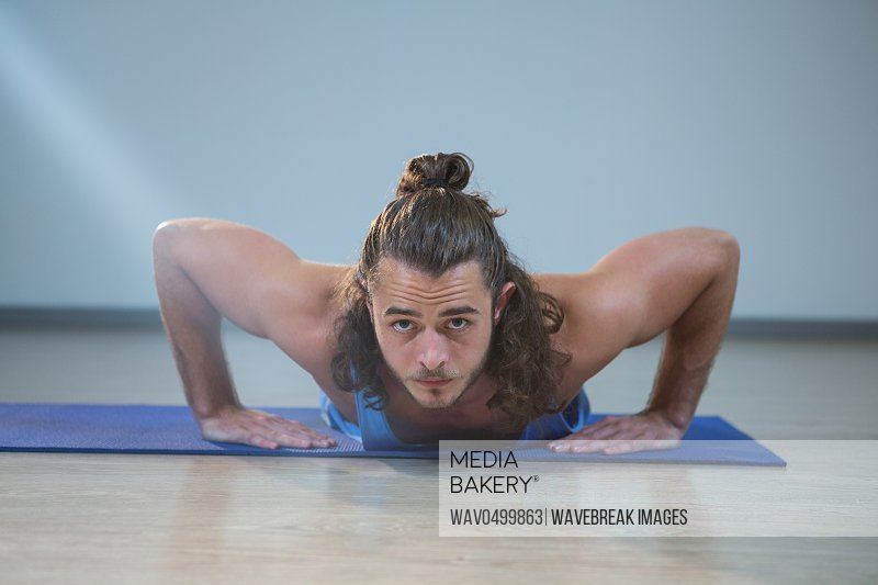 Portrait of man doing push-up on exercise mat in gym