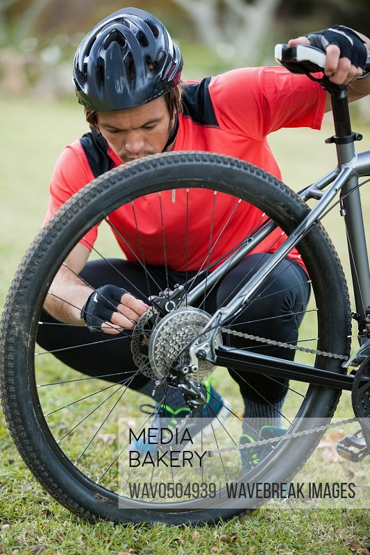 Male mountain biker fixing his bike chain in the forest
