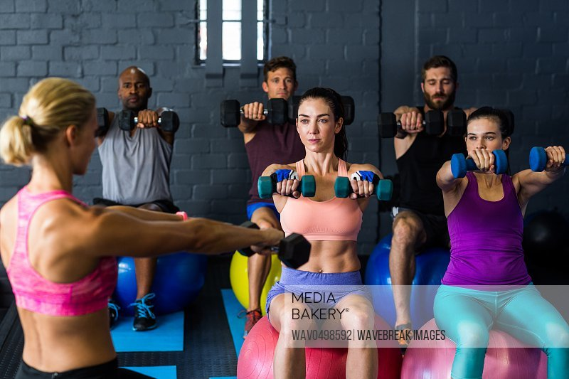 Male and female athletes exercising with trainer in gym