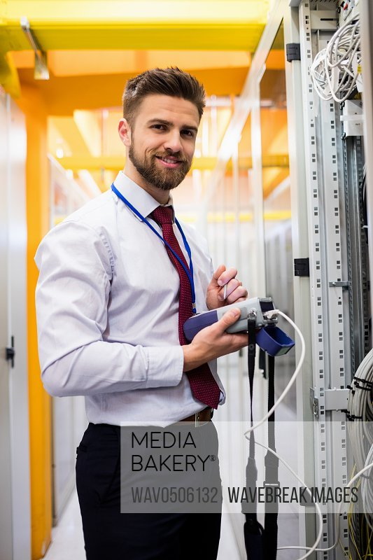 Portrait of smiling technician using digital cable analyzer in server room