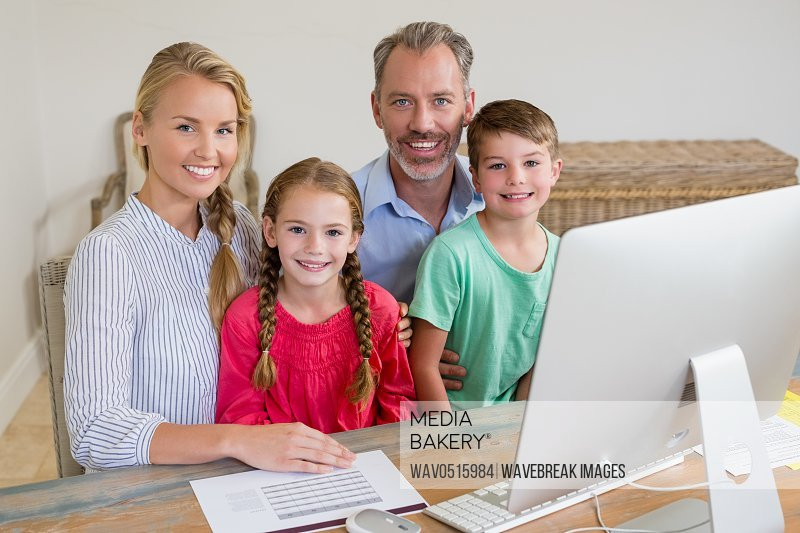 Happy family sitting at desk with computer