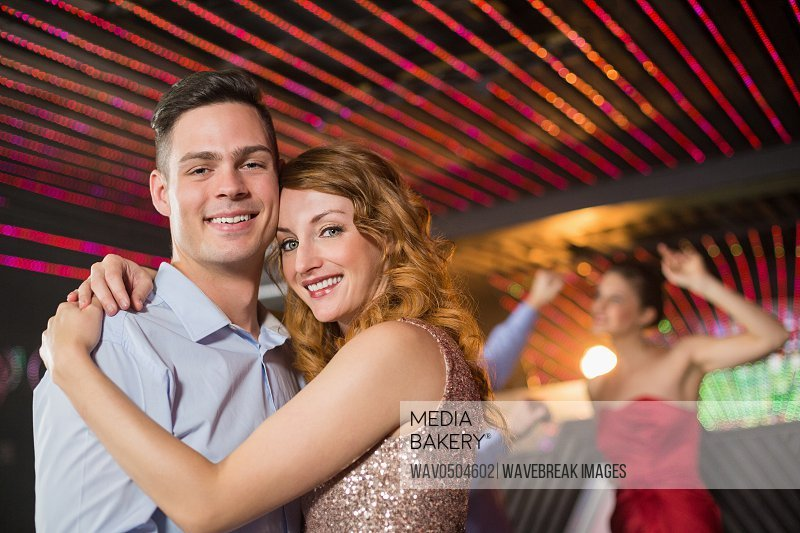 Portrait of smiling couple embracing each other in bar