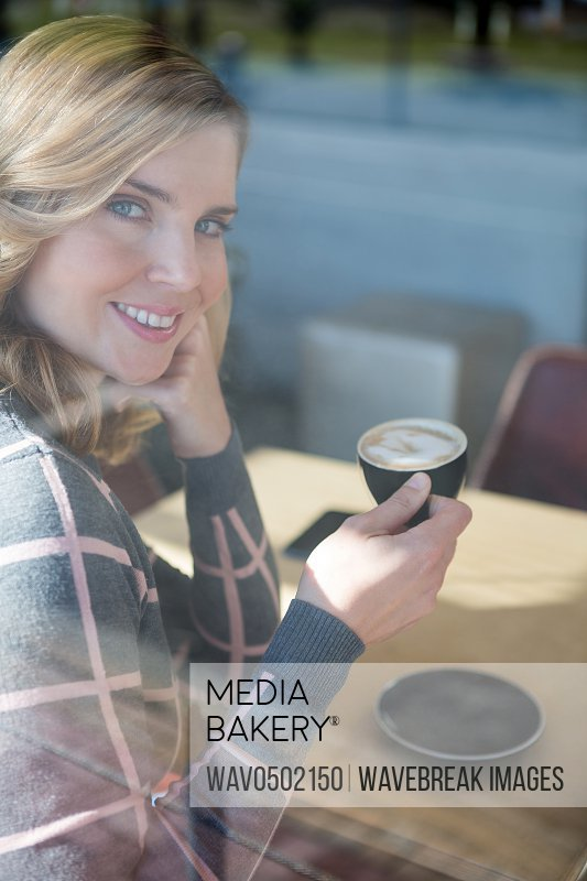 Portrait of smiling woman having coffee in cafeteria