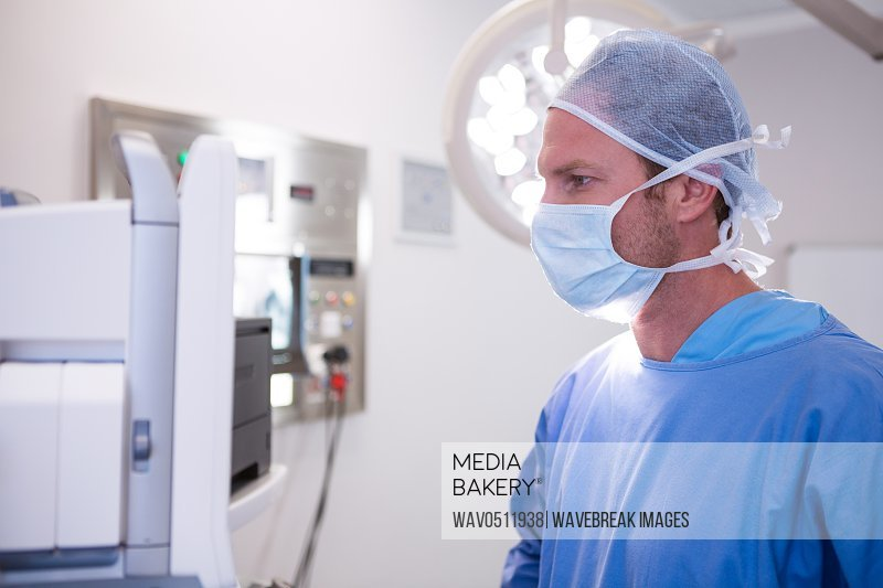 Male surgeon looking at machine in operation theater at hospital