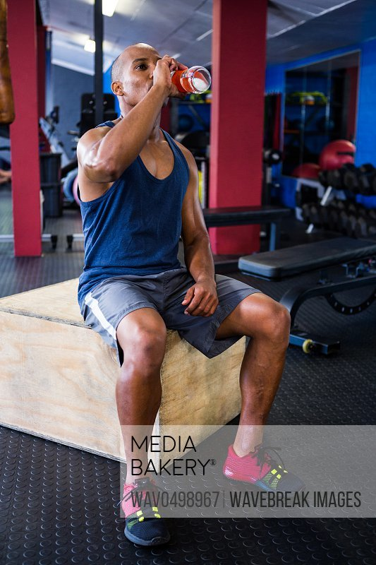Full length of male athlete drinking juice while sitting on wooden box in gym