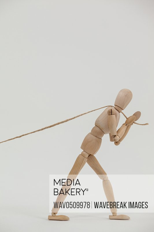 Wooden figurine pulling a rope against white background
