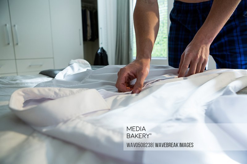 Man unbuttoning his white shirt in bedroom at home