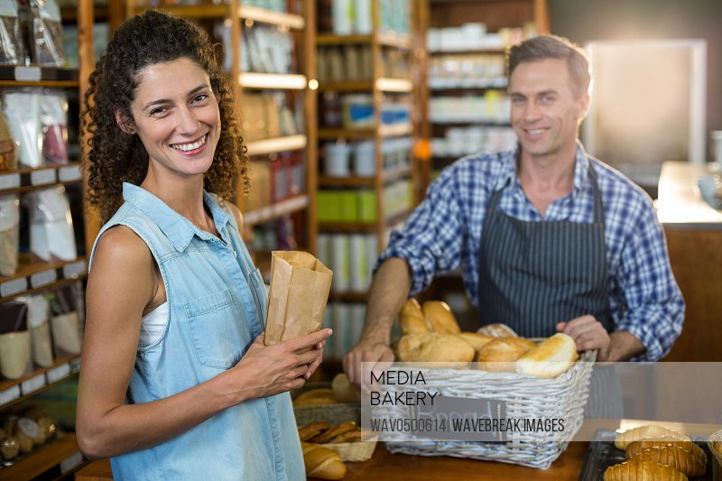 Portrait of smiling woman purchasing bread at bakery store in supermarket