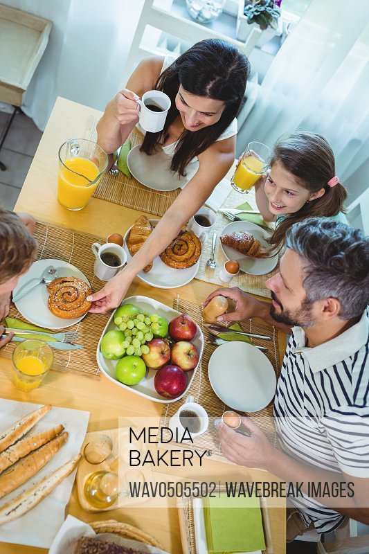 Overhead view of happy family having breakfast at home