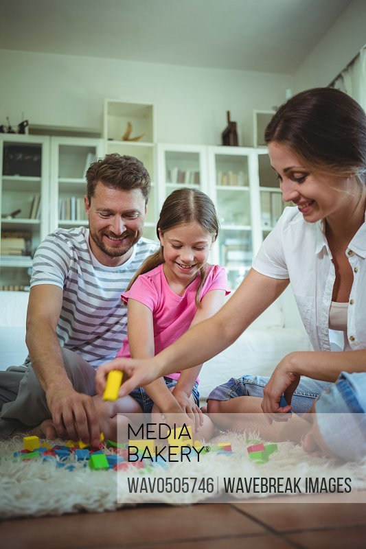 Parents and daughter playing with building blocks on the floor