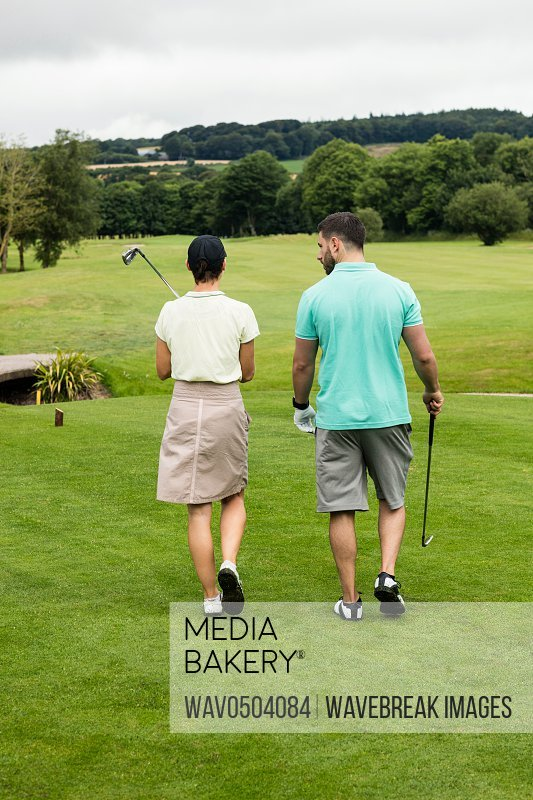 Rear view of couple walking on a golf course