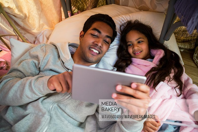 Father and daughter using digital tablet in the bedroom