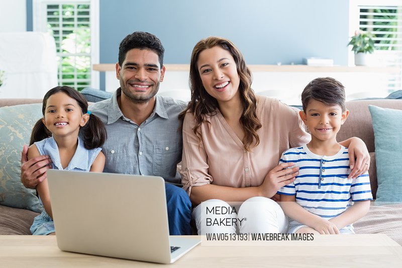 Portrait of happy parents and kids sitting with arm around in living room
