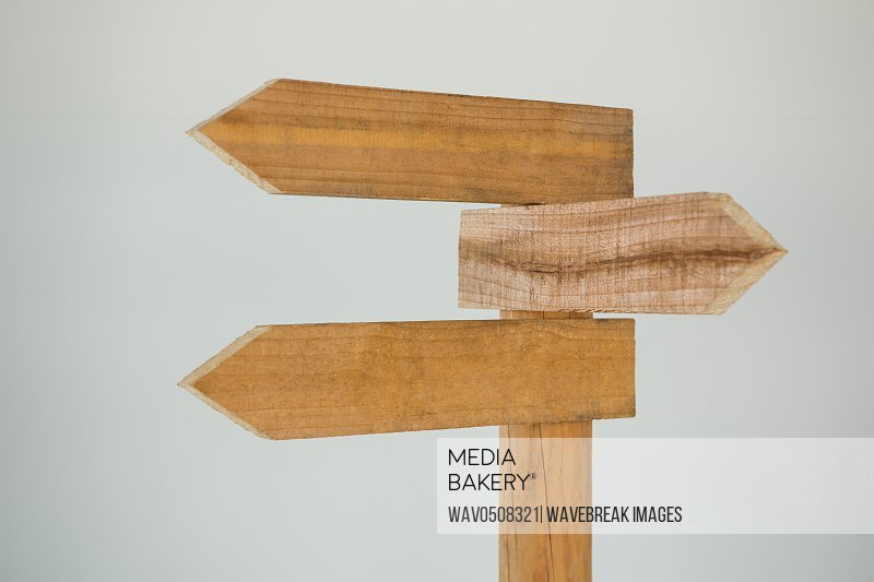 Wooden arrow direction sign post against white background