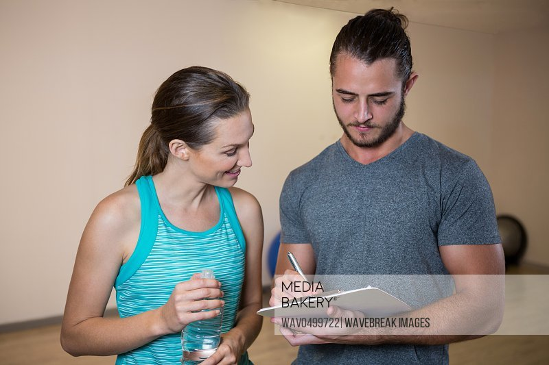 Fitness trainer and woman looking at clipboard in fitness studio