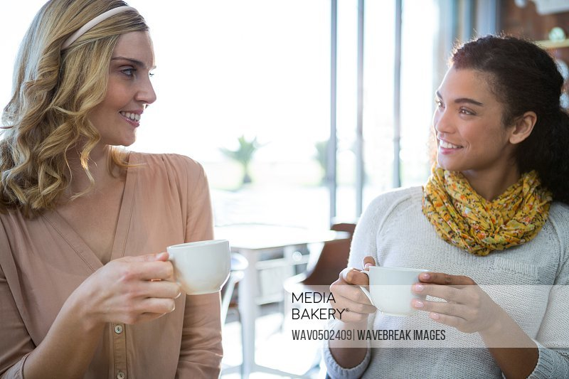 Smiling female friends sitting together and having coffee in coffee shop