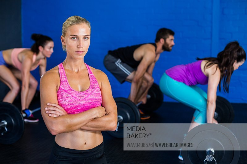 Portrait of confident woman standing while people exercising in background at gym