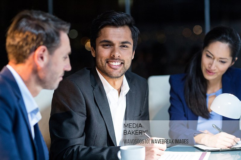 Businessman smiling at camera while colleagues looking at document in the office