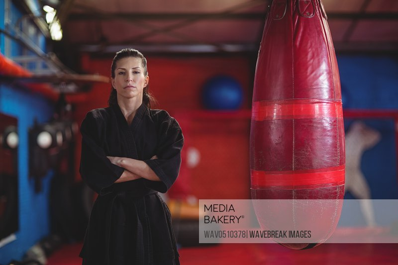 Female karate player standing with arms crossed in fitness studio