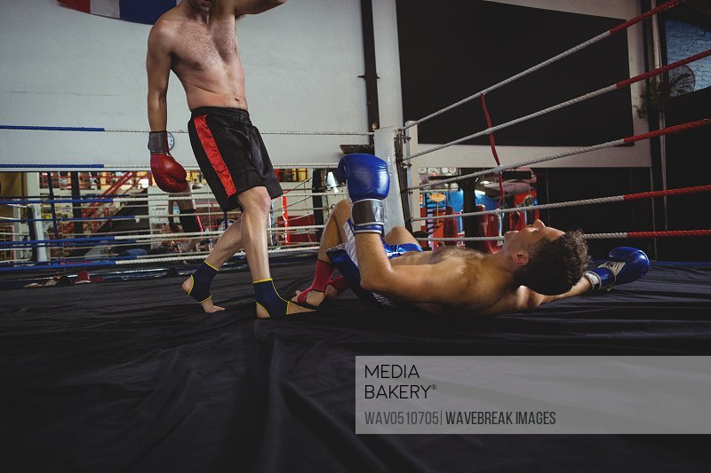 Boxers fighting in boxing ring at arena