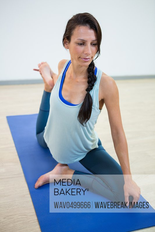 Woman in lord of the dance yoga pose in fitness studio