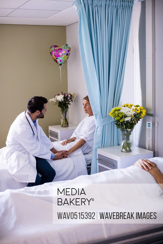 Male doctor consoling female senior patient