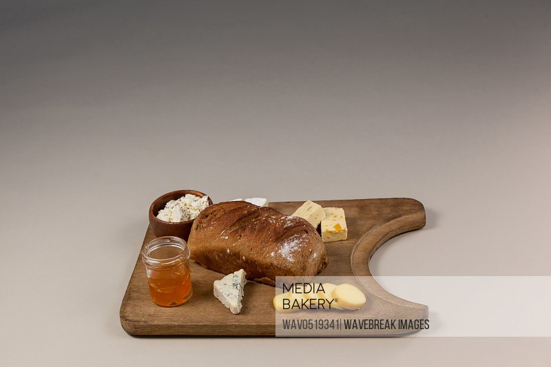 Variety of cheese with bread and sauce on chopping board