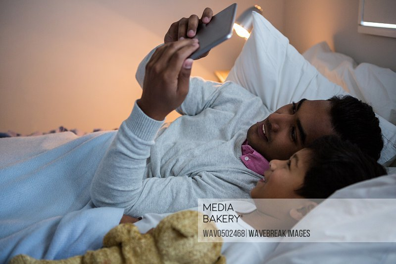 Father and son using digital tablet on bed in the bedroom