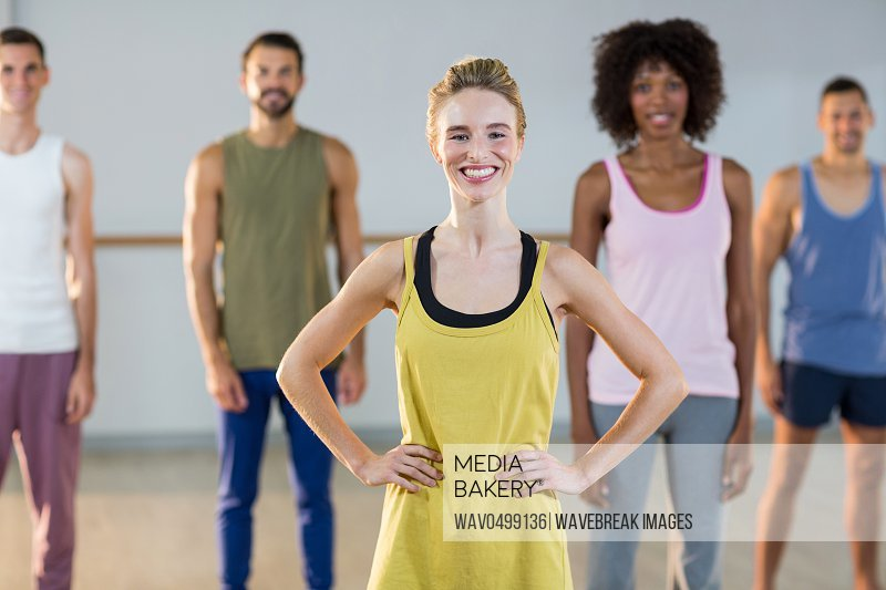 Portrait of instructor and students standing in fitness studio