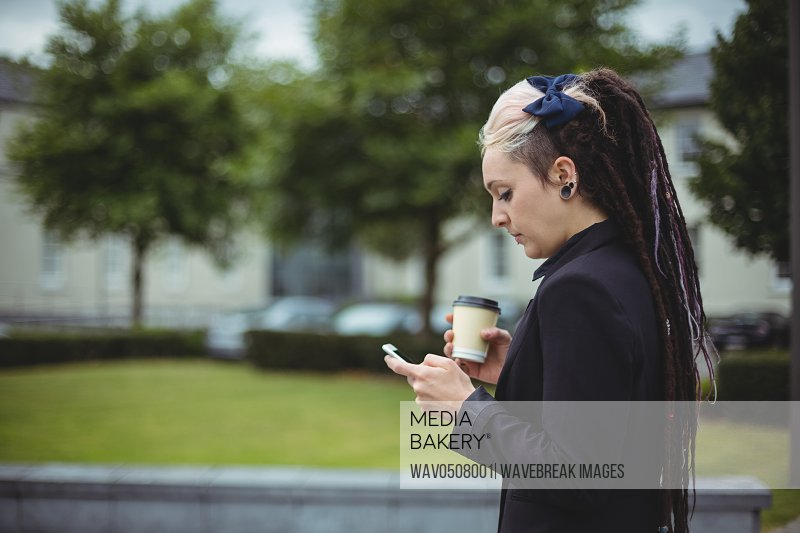 Businesswoman using mobile phone in office campus