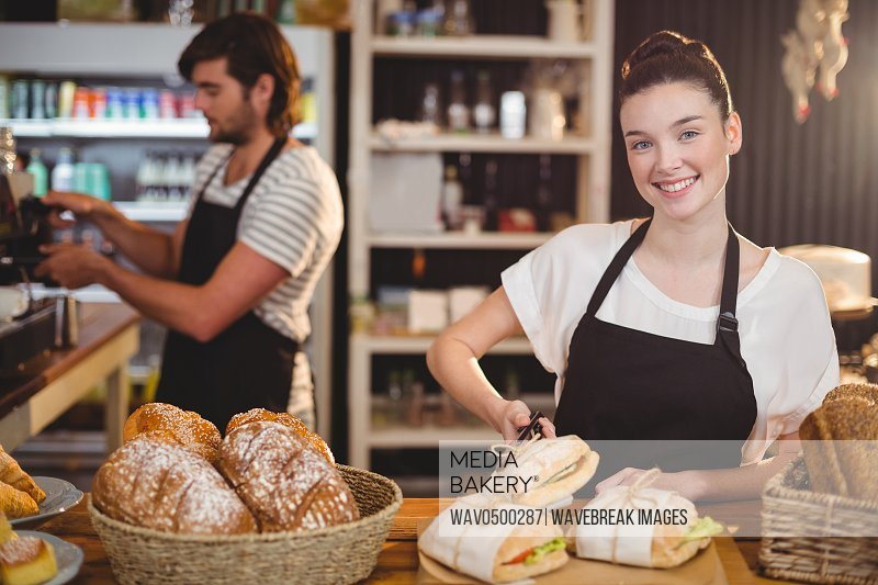 Portrait of waitress standing at counter with sandwiches and bread roll in cafe