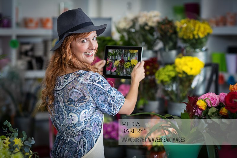 Portrait of female florist taking photograph of flowers from digital tablet in flower shop