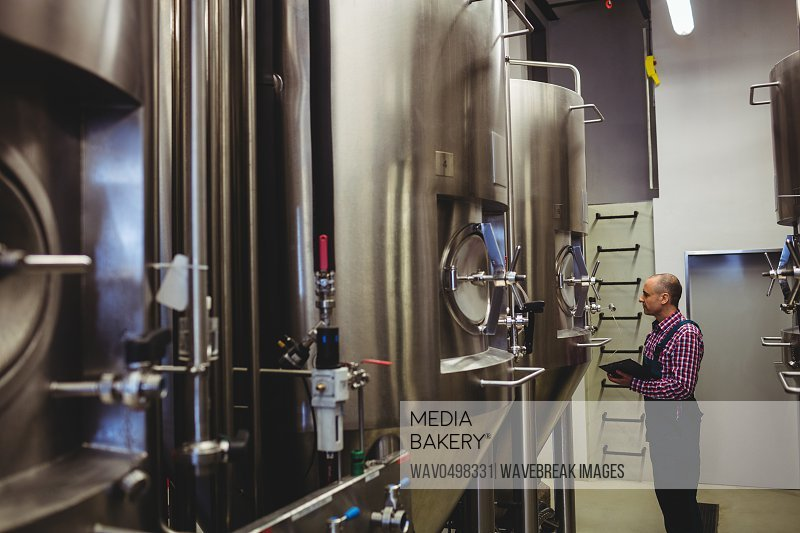 Side view of owner examining machinery at brewery