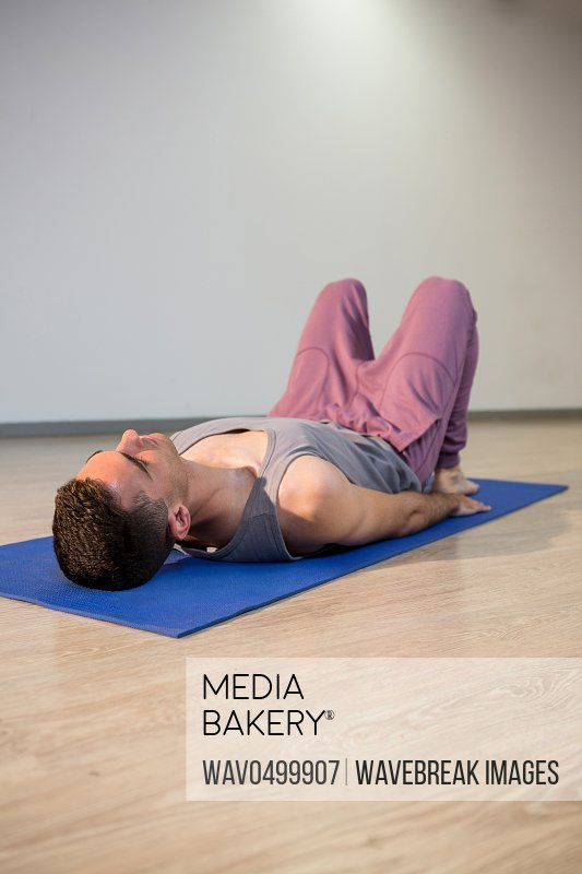 Man in yoga corpse pose in gym