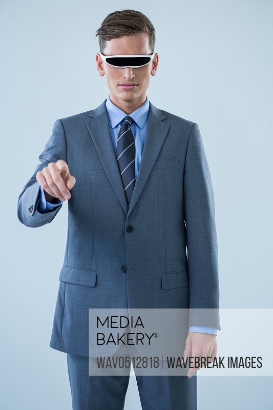 Businessman pointing his finger while using virtual reality glasses against white background
