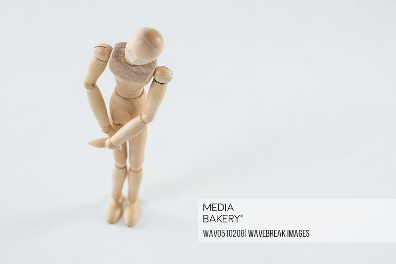 Wooden figurine with leg injured against white background