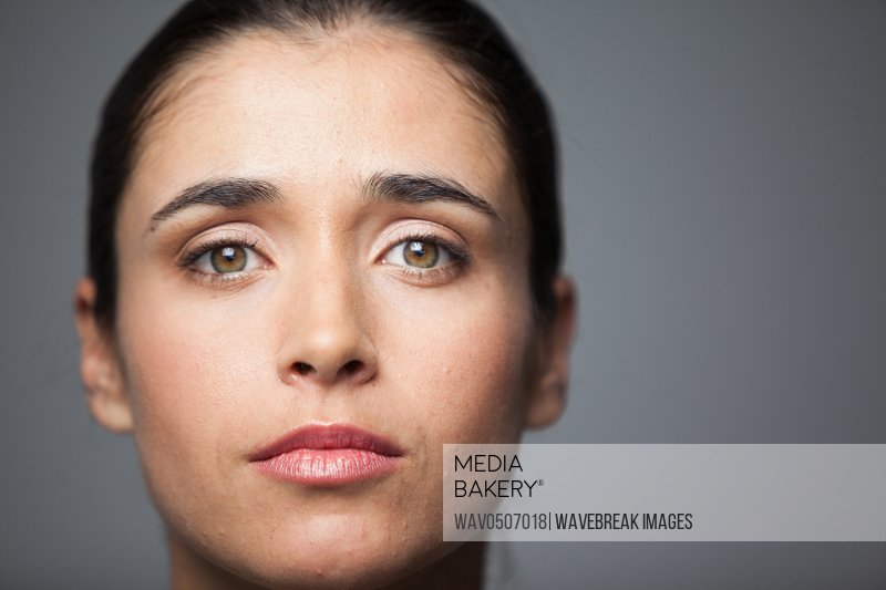 Portrait of woman wearing contact lens against grey background