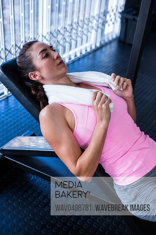Thoughtful athlete lying on bench press in gym