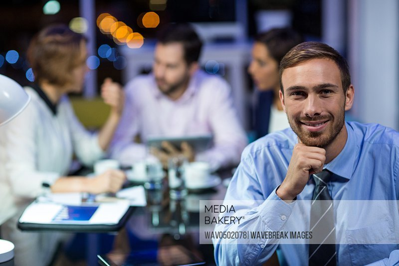 Portrait of smiling businessman in office at night