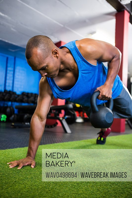 Athlete holding kettlebell while exercising in gym