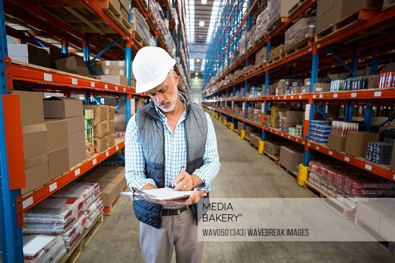 Warehouse worker writing on clipboard in warehouse